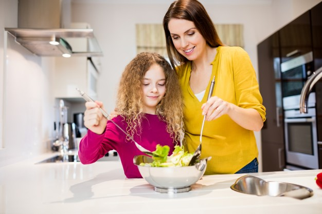 mother-assisting-daughter-in-making-salad_1170-2805